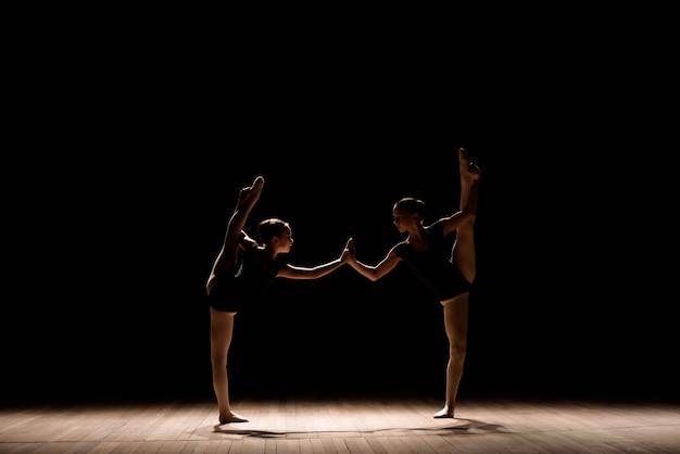 Flexibele ballerina's strekken zich uit over een scène met een donkere achtergrond