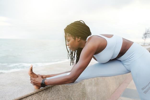 Flexibele fit jonge sportvrouw die de benen op de kade strekt na het joggen in de ochtend