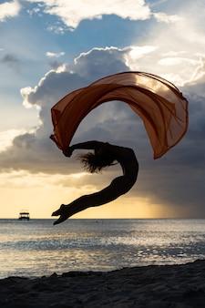 Flexibele fit vrouw springen met zijde tijdens dramatische zonsondergang met stormachtige wolken. concept van individualiteit, creativiteit en zelfvertrouwen.
