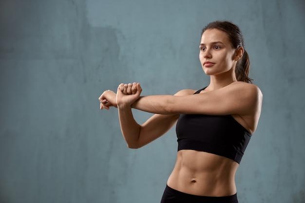 Flexibele fitnesswoman arm uitrekken voordat training