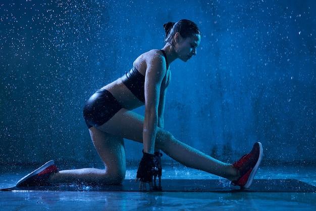 Flexibele fitnesswoman die zich uitstrekt voor de training