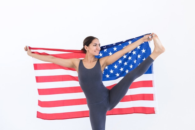 Flexibele gelukkige vrouw atleet amerikaanse vlag usa onafhankelijkheidsdag 4 juli