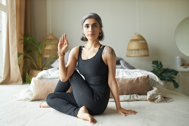 Flexibele jonge gevorderde vrouwelijke yogi met voortijdig grijs haar zittend op de vloer in ardha matsyendrasana houding, zittend spinale draai om de spijsvertering te verbeteren en rugpijn te verlichten