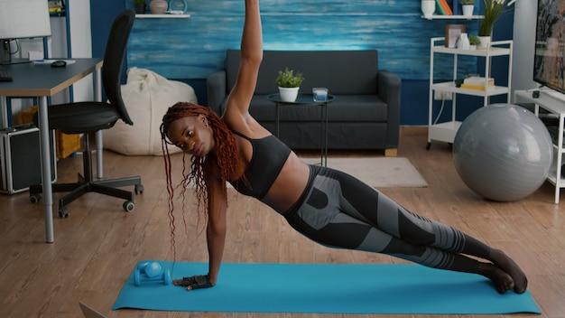 Flexibele jonge vrouw die op yogakaart in woonkamer opwarmt die zich in zijplank bevindt die online aërobe video op laptop computer kijkt