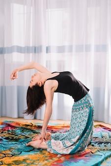 Flexibele jonge vrouw die yoga doet bij gymnastiek