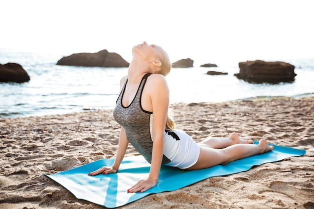 Flexibele jonge vrouw die yoga-oefeningen doet op het strand