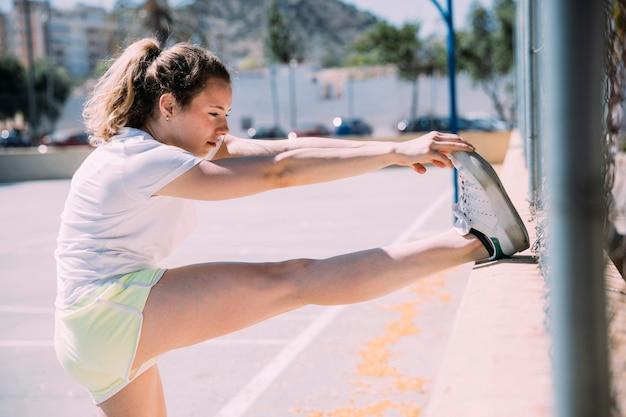 Flexibele jonge vrouw die zich uitstrekt been