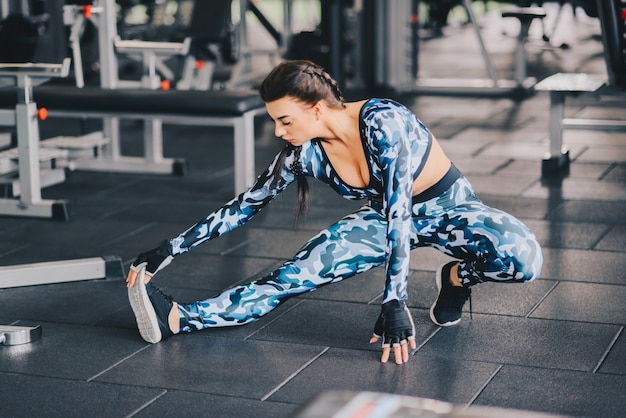 Flexibele jonge vrouw haar rechterbeen in de sportschool uitrekken. gezonde levensstijl. fitness concept. copyspace