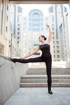 Flexibele jonge vrouw in zwarte sportsuit poseren met opgeheven hand