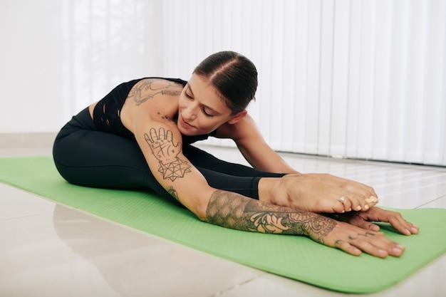 Flexibele jonge vrouw training in dansstudio, zittend op een yogamat en naar voren buigen