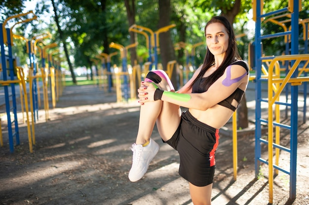 Flexibele prachtige gespierde vrouw, gekleed in zwarte sport-outfit