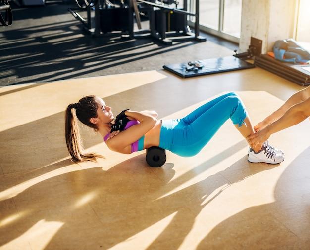 Flexibele slanke jonge vrouw doet oefening met een schuimroller in de zonnige sportschool met hulp van een personal trainer.