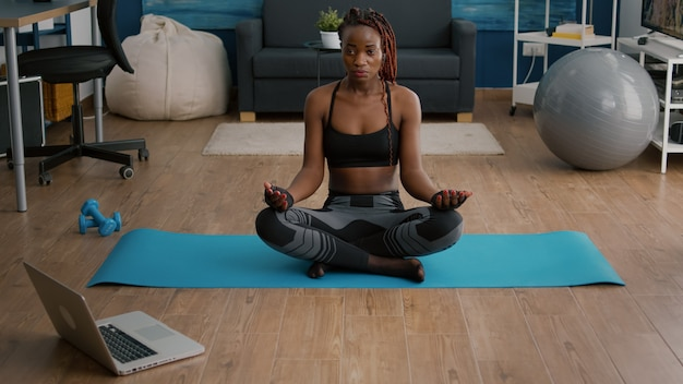 Flexibele slanke zwarte vrouw zittend in lotuspositie op yoga kaart in woonkamer
