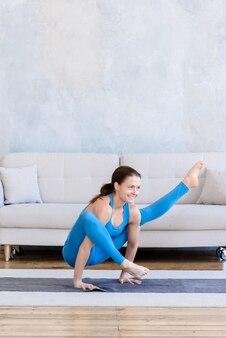 Flexibele sportieve vrouw sporten thuis training yoga die zich uitstrekt op de mat in de kamer