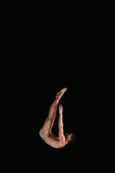 Flexibele sportman die op zwarte achtergrond vliegt