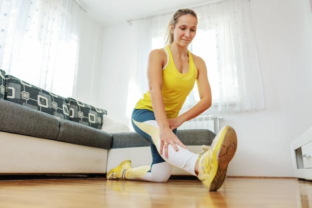 Flexibele sportvrouw die thuis rek- en fitnessoefeningen doet tijdens het coronavirus.