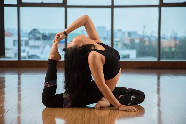 Flexibele vrouw die op vloer danst