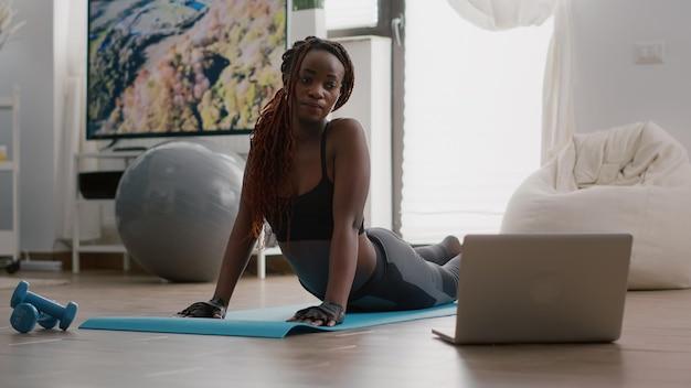 Flexibele zwarte vrouw die sport beoefent tijdens yoga ochtendtraining zittend op fitnesskaart in de woonkamer. volwassen lichaamsspieren die zich uitstrekken kijken naar training aerobe video met behulp van laptopcomputer