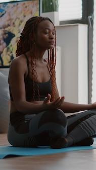 Flexibele zwarte vrouw die zich uitstrekt spier beoefenen gymnastiek in de ochtend zittend in lotushouding op...