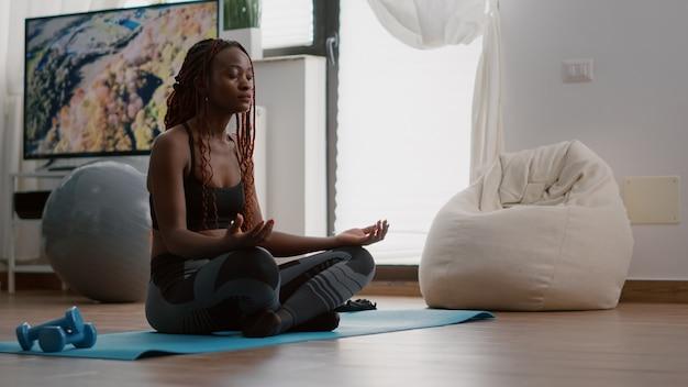 Flexibele zwarte vrouw die zich uitstrekt van de spier die 's ochtends gymnastiek beoefent