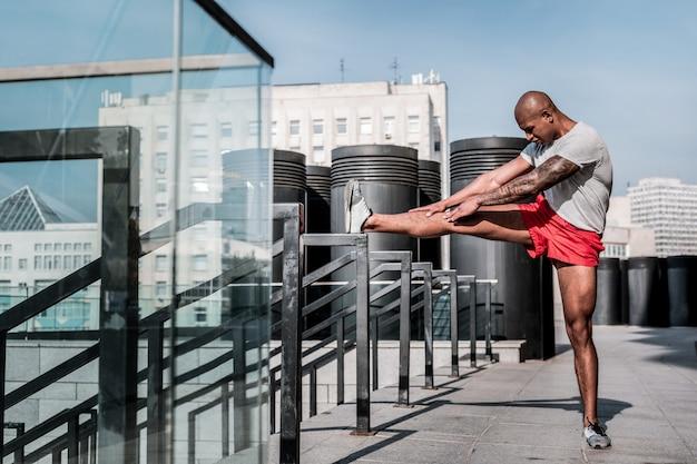Flexibiliteitsoefening. knappe ernstige sportman die zijn tenen probeert aan te raken terwijl hij een flexibiliteitsoefening doet