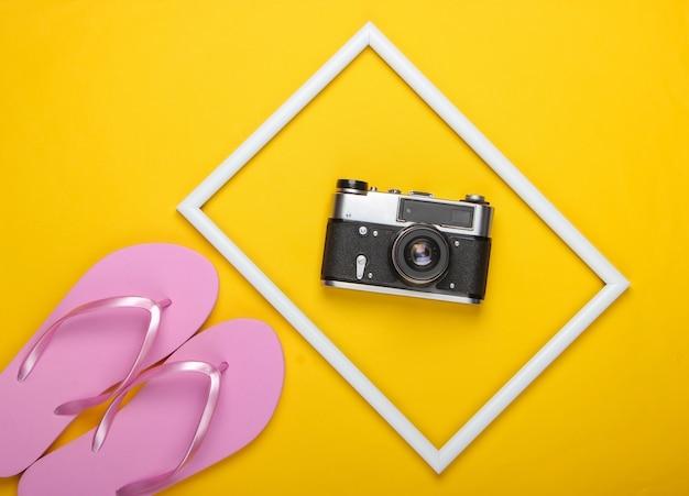 Flip flops en retro camera op geel oppervlak met wit frame