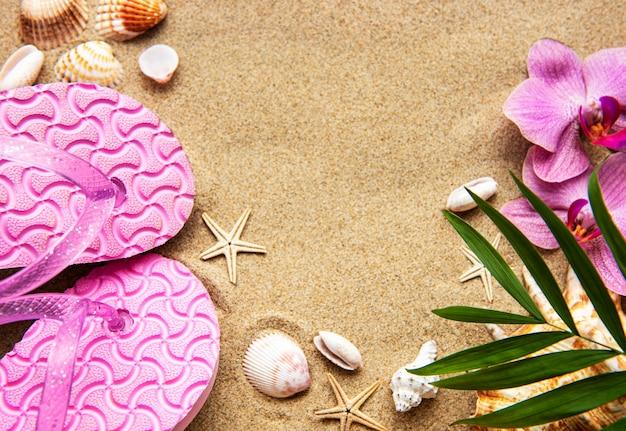 Flip flops in het zand met zeesterren en orchideebloemen