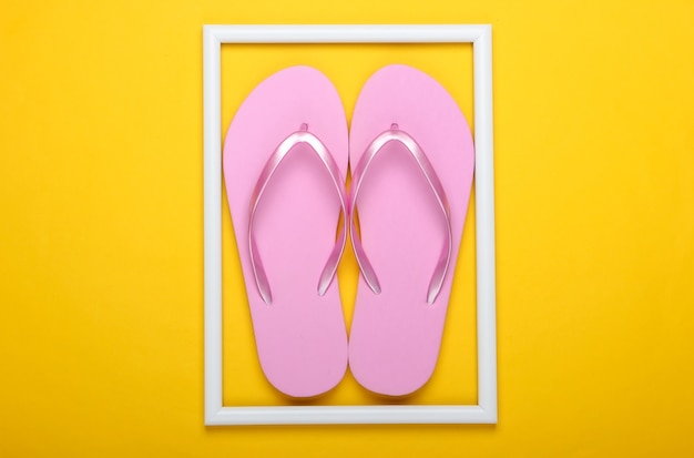 Flip flops op geel oppervlak met wit frame