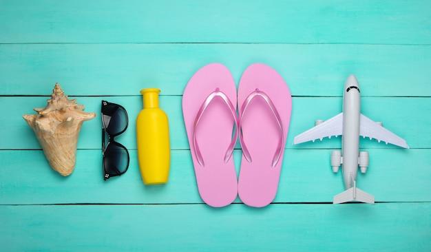 Flip flops, vliegtuig, zonnebril, fles sunblock, zeeschelp op een blauwe houten