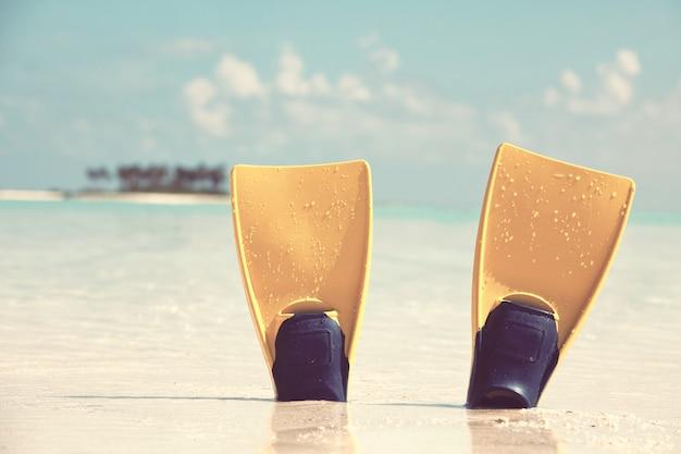 Flippers op zand aan de rand van de zee in het eiland van de maldiven