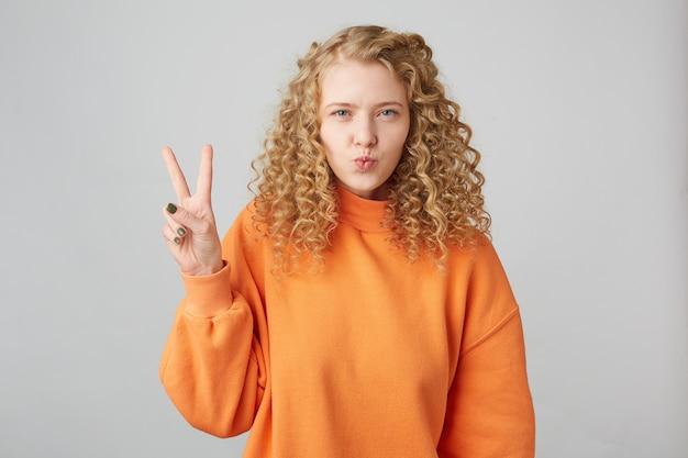 Flirtende blonde met krullend haar met blauwe ogen zendt luchtkus met pount-lippen, toont met haar vingers een vredesteken of overwinning