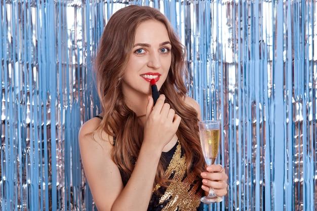 Flirtende vrouw met champagne past rode pommade toe op de lippen en kijkt rechtstreeks naar de camera, poseren geïsoleerd over blauwe muur met zilveren klatergoud
