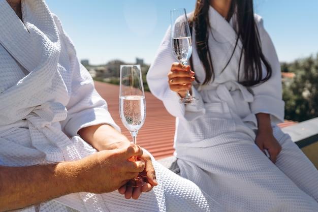 Flirterend paar met mousserende wijn op een dak