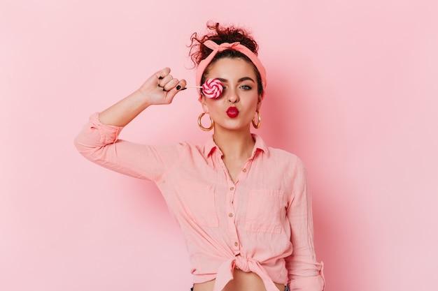Flirterig donkerharig meisje in roze hoofdband en enorme oorbellen bedekt oog met snoep.