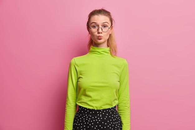Flirterig meisje blijft op een glamoureuze manier lippen vouwen, ziet knappe jongen, flirt, wil iemand kussen, draagt groene coltrui, ronde grote bril