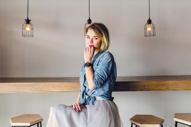 Flirterige blonde vrouw met blauwe ogen en felroze lippen, zittend in een coffeeshop op een stoel die koffie drinkt