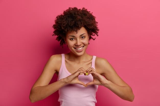 Flirterige, gelukkige jonge krullende vrouw drukt liefde en genegenheid uit, maakt een hartgebaar, laat zien wat je voor haar betekent, bedankt lieve vriend voor hulp, heeft een charmante tedere blik, poseert tegen een roze muur