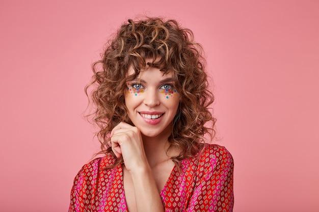 Flirterige jonge vrouw die kijkt, op een lip bijt, koket kijkt, gestreepte roze en oranje kleren draagt, haar haar aanraakt, staand