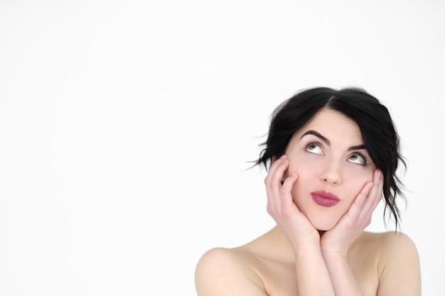 Flirterige koket vrouw met hoofd in handen en opzoeken op witte muur.