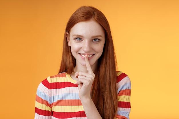 Flirterige slinkse creatieve jonge roodharige lachend opgewonden gember meisje bereid mysterieus cadeau verrassingsfeestje giechelen lastig zeg zwijgen shhh gebaar wijsvinger mond grijnzend opgetogen, heb een idee. Premium Foto