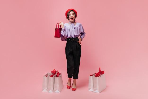 Flirterige vrouw gekleed in een stijlvolle broek met hoge taille en heldere baret vormt met kleine handtas en pakketten op roze achtergrond.