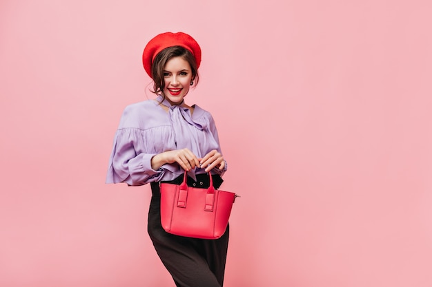Flirterige vrouw in baret, blouse en broek met rode tas op roze achtergrond.