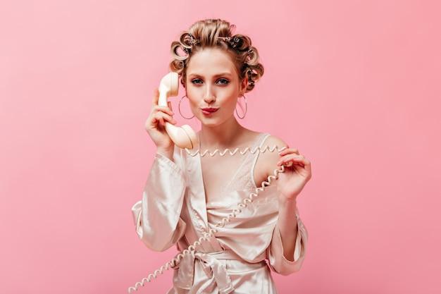 Flirterige vrouw met haarkrulspelden bijt op haar lip en praat over vaste telefoon op roze muur