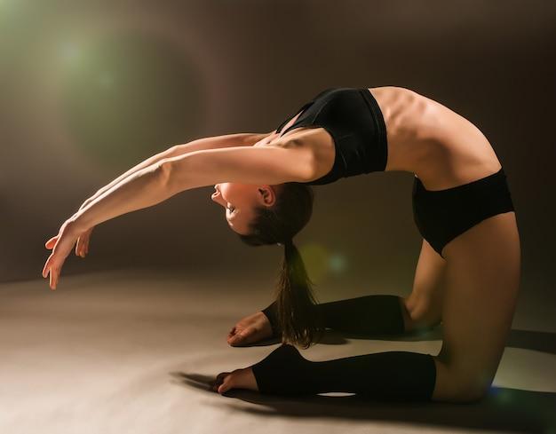 Fllexible atletische jonge mooie vrouw in sportkleding maakt een bocht poseren in de studio tegen een donkere achtergrond. concept van een gezond atletisch lichaam. advertentie ruimte