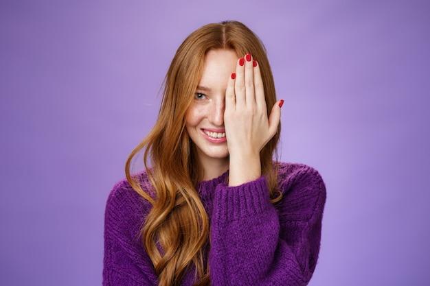 Fllirty en gelukkig aantrekkelijk gembermeisje dat met één oog gluurt terwijl het een half gezicht bedekt met palm, dromerig glimlachend van geluk en speelse stemming, blij en zorgeloos poserend over paarse achtergrond.