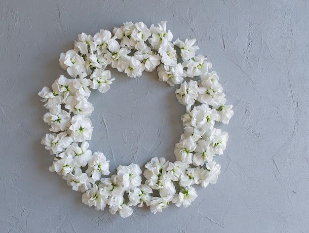 Floral frame met kleine witte bloemen op grijze tafel.