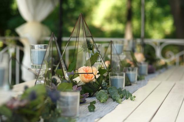 Florarium met verse, sappige en roze bloemen feestelijke tafeldecoratie