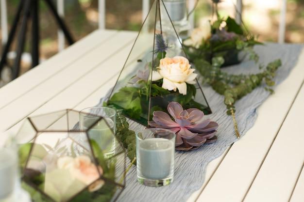 Florarium met verse succulente en roze bloemen feestelijke tafeldecoratie.