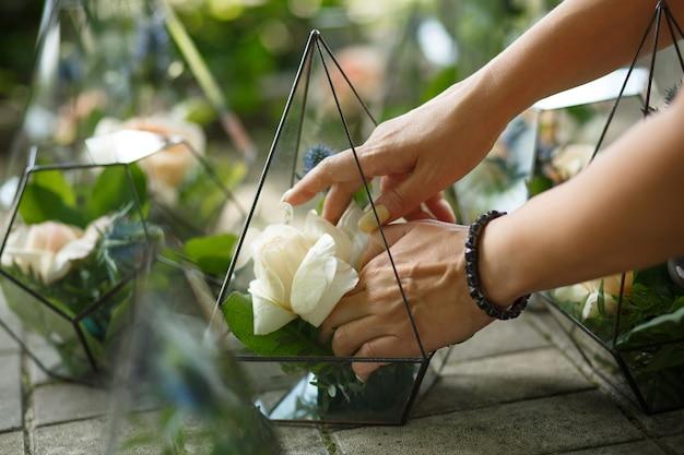 Florarium met verse succulente en roze bloemen