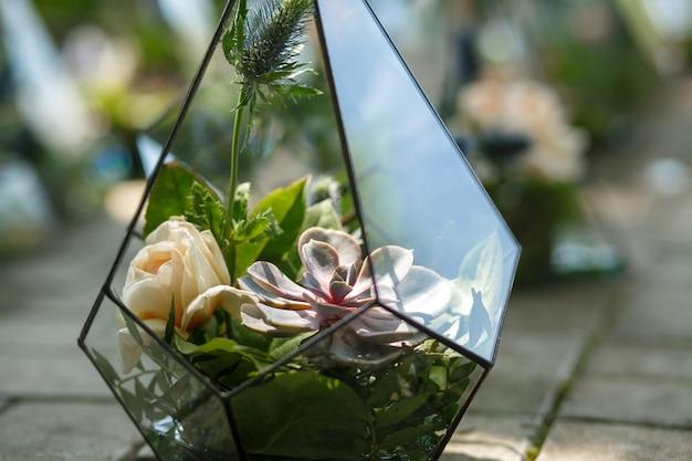 Florarium met verse succulente en roze bloemen.
